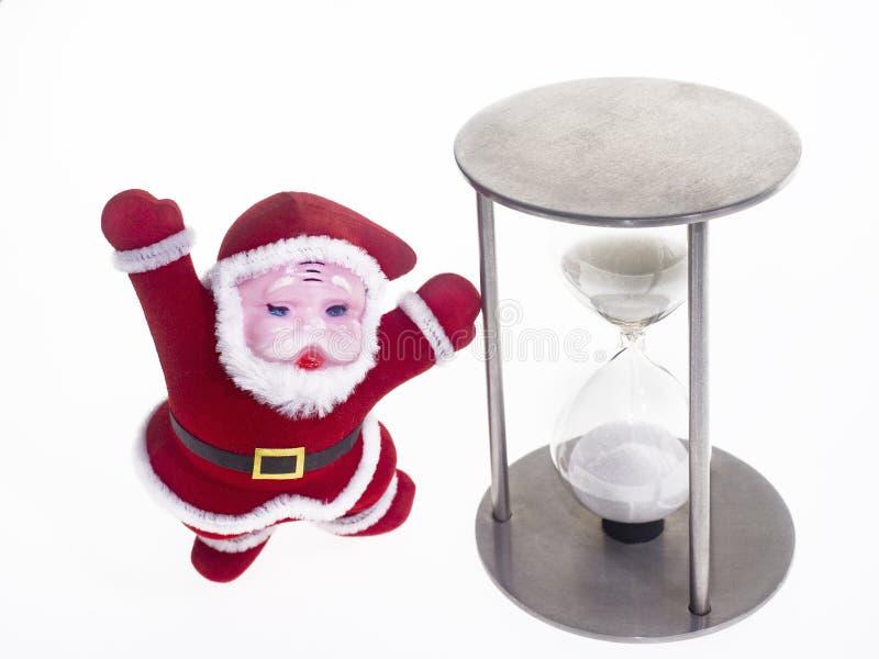 Santa Claus in un vestito rosso tradizionale indica una clessidra isolato immagine stock libera da diritti