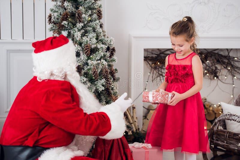 Santa Claus und Kinder, die Geschenke am Kamin öffnen Kinder bringen in tragenden offenen Geschenken Bart des Kostüms Weihnachtsh stockfotos