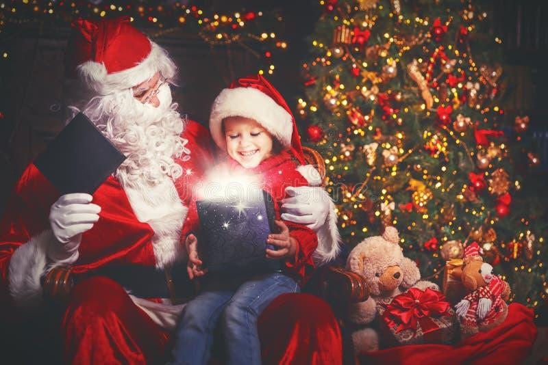Santa Claus- und Kindermädchen mit hellem magischem Geschenk im Weihnachten lizenzfreies stockfoto
