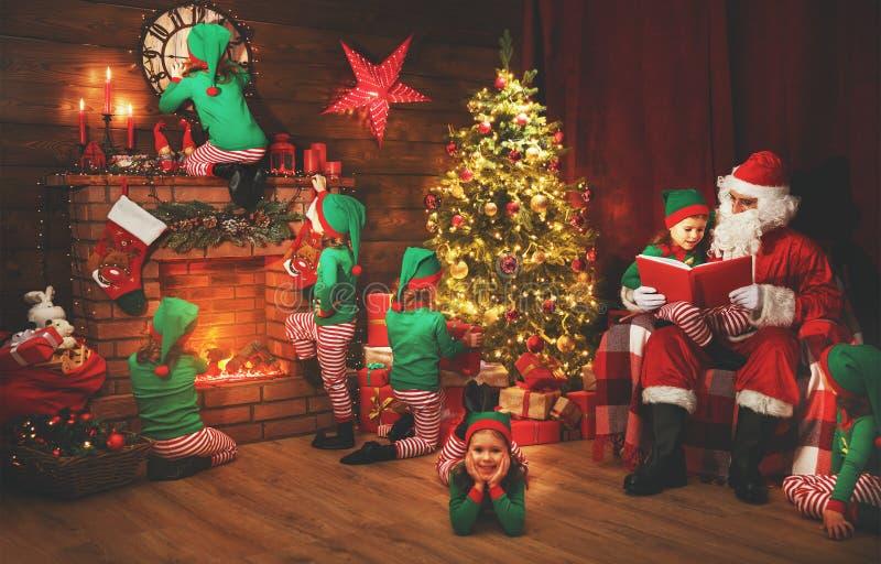 Santa Claus und kleine Elfen vor Weihnachten in seinem Haus lizenzfreies stockbild