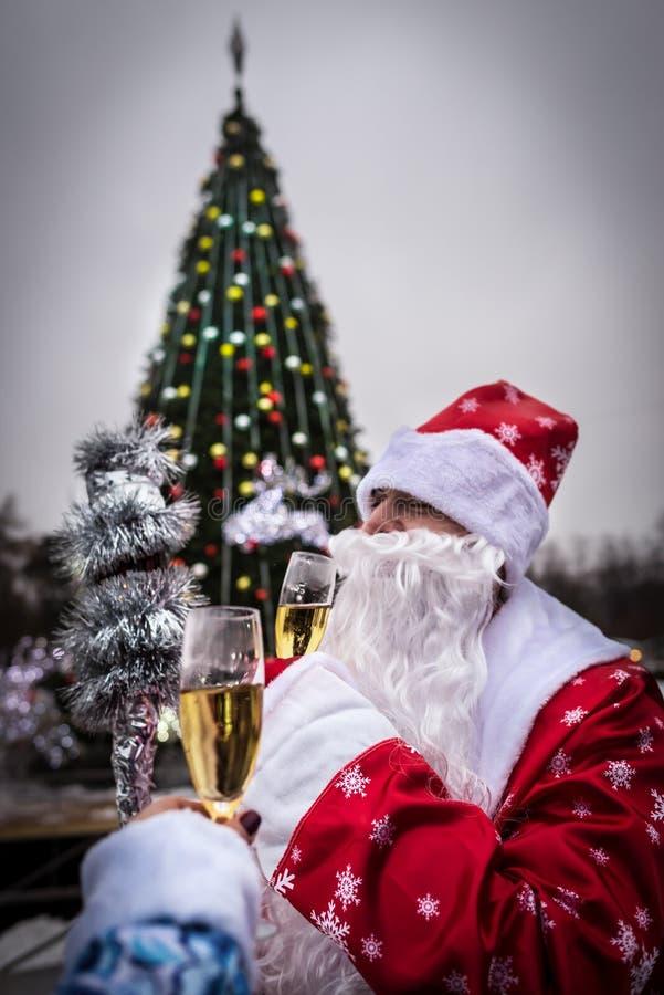 Santa Claus und Schnee-Mädchen feiert neues Jahr nahe Weihnachtsbaum lizenzfreies stockfoto
