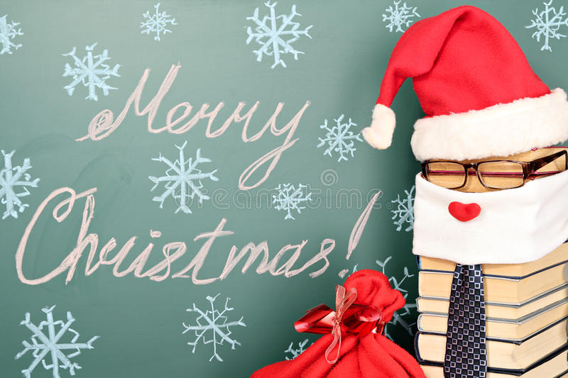 Santa Claus. Unusual Santa Claus from books with bag of gifts before blackboard with title MERRY CHRISTMAS royalty free stock image