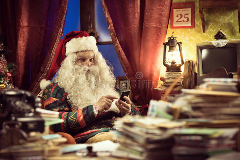 Santa Claus using smartphone. Funny Santa Claus using his new smartphone and relaxing at home stock photo