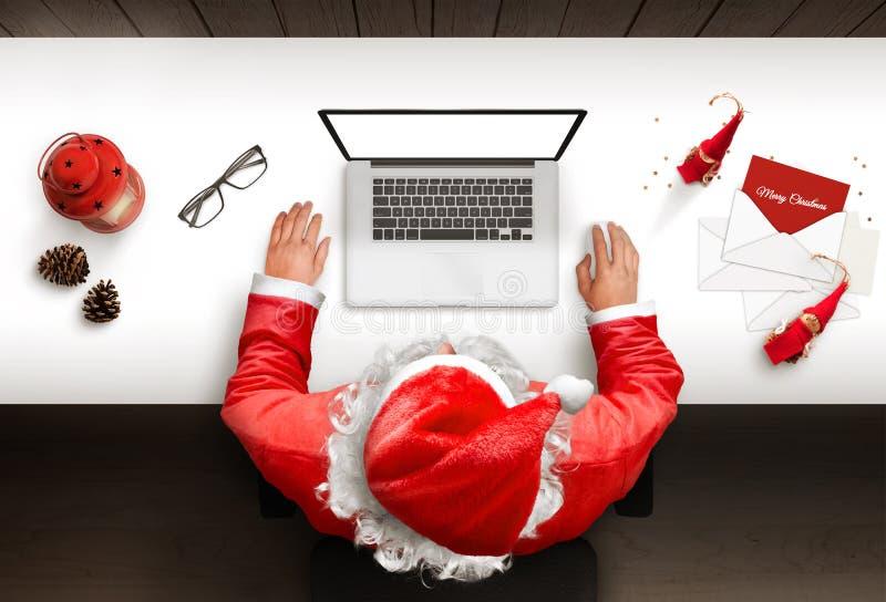 Santa Claus utiliza un ordenador portátil con la pantalla aislada, en blanco para la maqueta, presentación del sitio web fotografía de archivo