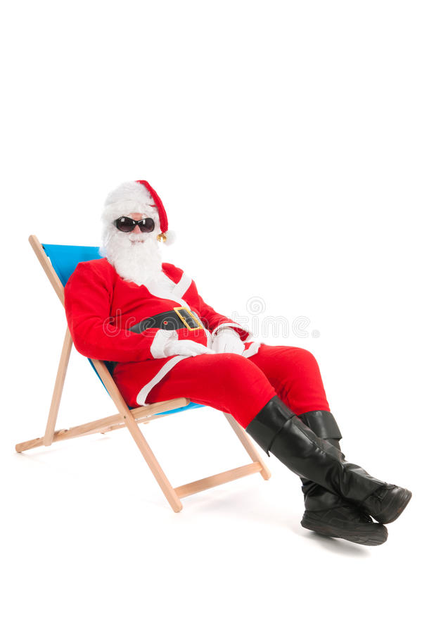 Santa Claus on vacation. Santa Claus in beach chair on vacation isolated over white background royalty free stock images