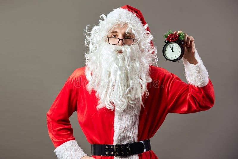 Santa Claus in vetri tiene l'orologio un orologio che mostra cinque - dodici in sua mano sui precedenti grigi fotografie stock
