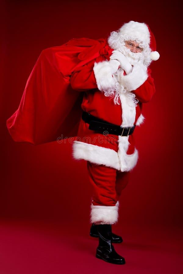 Santa Claus viene con una grande borsa dei regali Ritratto integrale fotografia stock