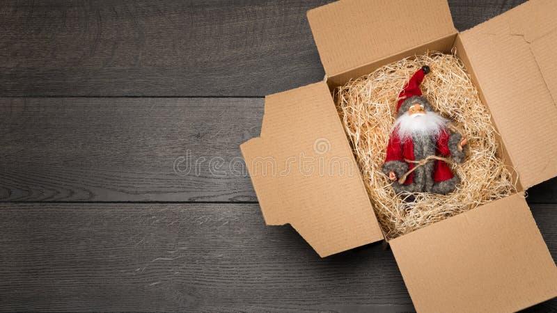 Santa Claus vilar på wood ull i en paperboardask efter jul arkivbild