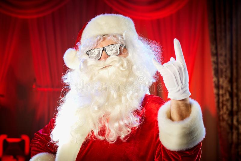 Santa Claus visar att en hand en skurkroll vaggar symbol royaltyfri fotografi