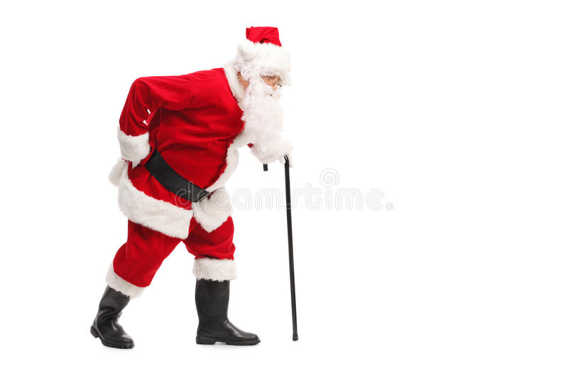 Santa Claus walking with a cane. Profile shot of Santa Claus walking with a cane and experiencing back pain isolated on white background stock photography