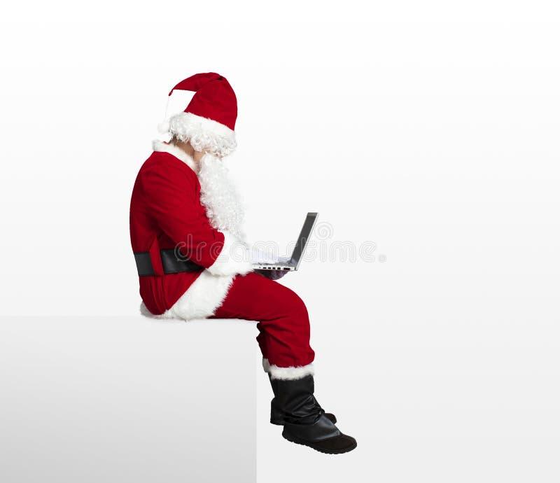 Santa claus watching laptop and sitting. On blank panel royalty free stock photos