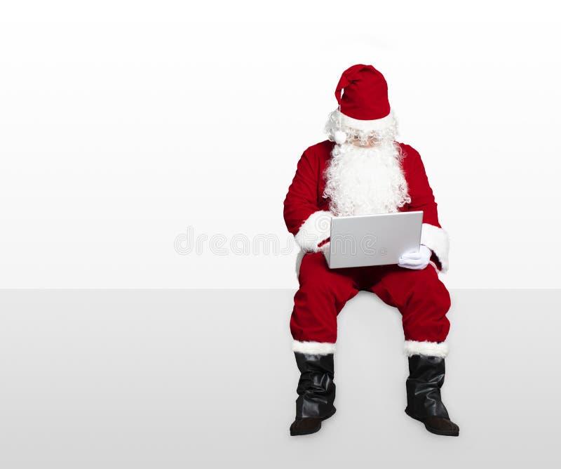 Santa claus watching laptop and sitting. On blank panel stock photos