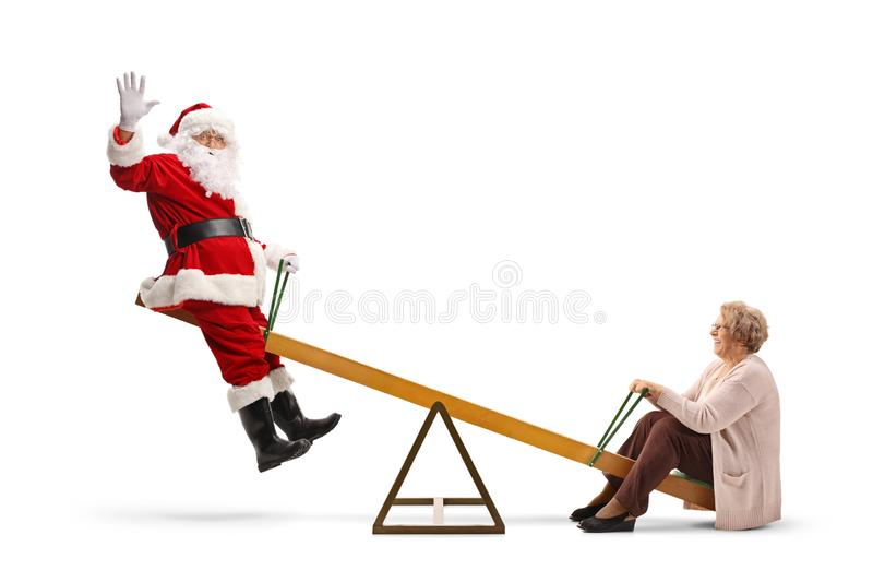 Santa Claus waving and playing on a seesaw with a happy senior woman royalty free stock photo