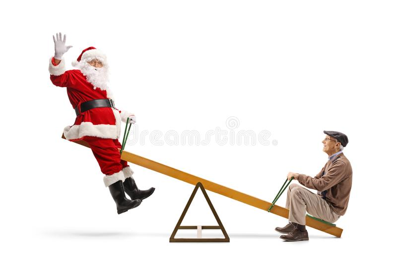 Santa Claus waving and playing on a seesaw with a senior man royalty free stock photos