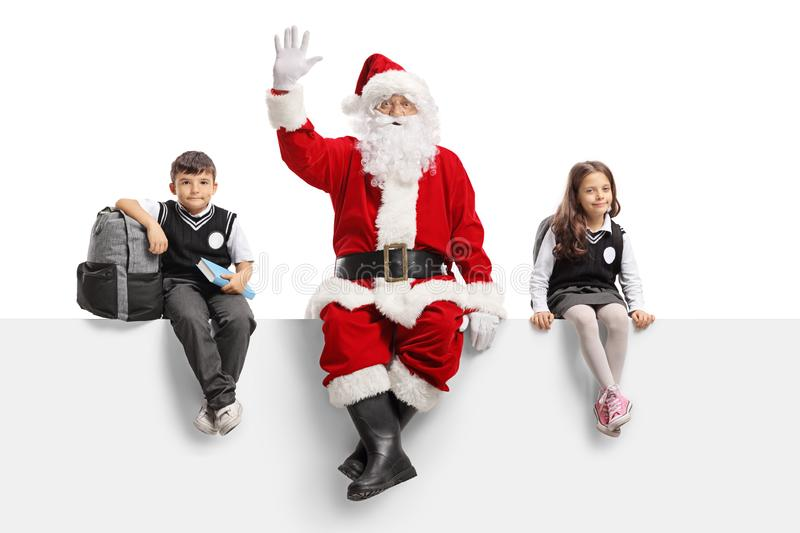 Santa Claus waving and sitting on a panel with schoolchildren. Isolated on white background stock photo