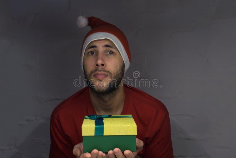 Santa Claus, Weihnachten, neues Jahr, Feiertag, Winter Überraschter bärtiger Mann in Santa Claus-Hut auf rotem Hintergrund Frohe  lizenzfreie stockfotos