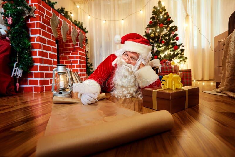 Santa Claus am Weihnachten, neues Year& x27; s Eve schrieb eine Liste von Geschenken t stockfotografie