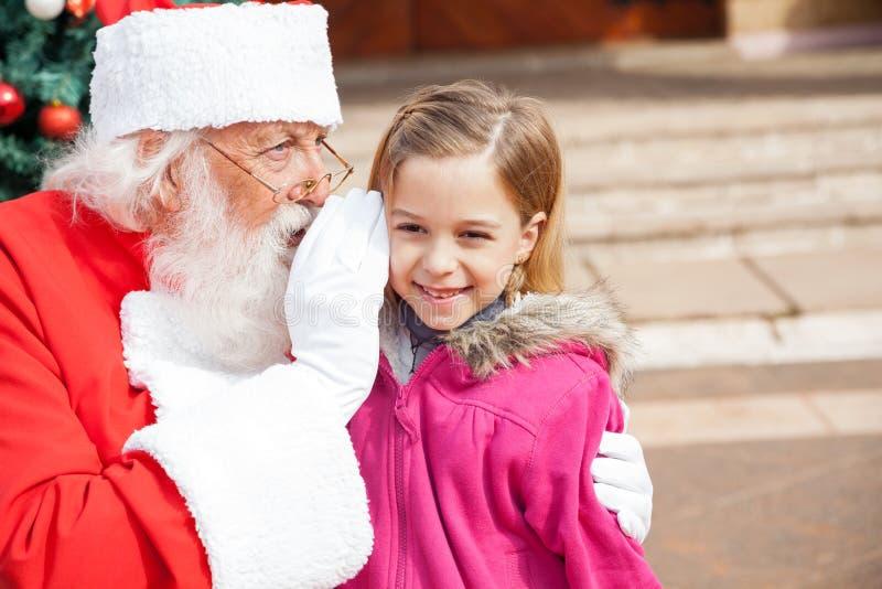 Santa Claus Whispering In Girls Ohr stockbild