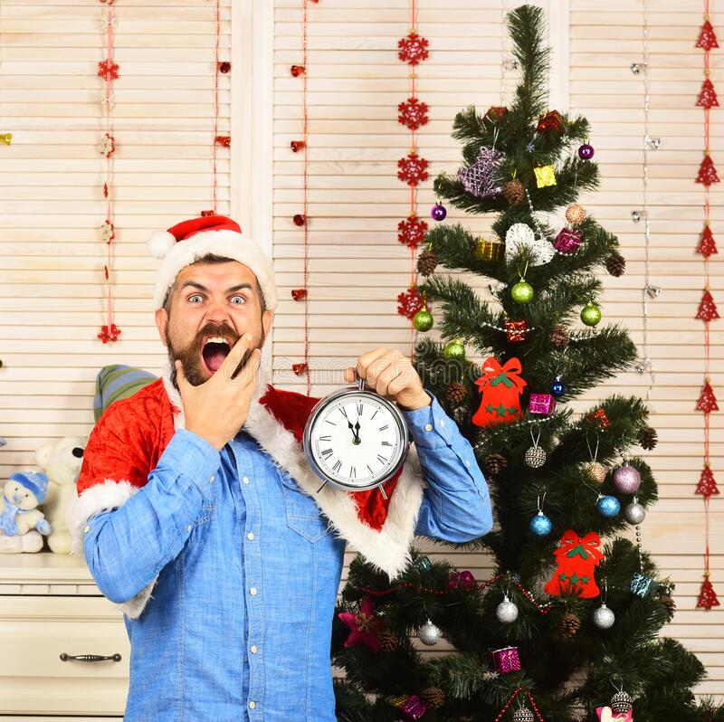 Santa Claus with wild face near Christmas tree on background royalty free stock photo