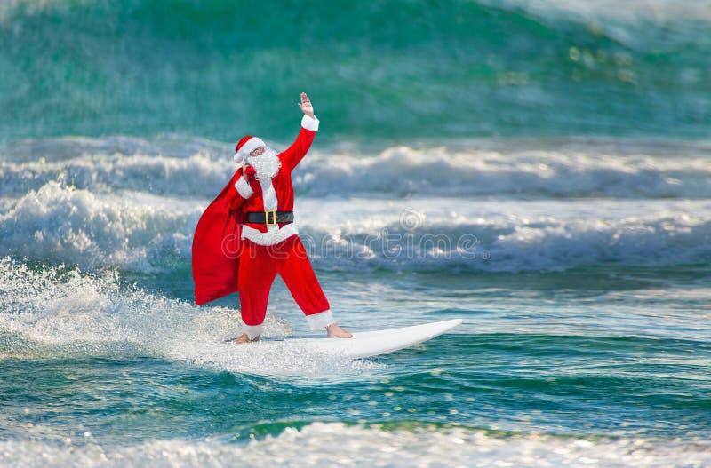 Santa Claus windsurfer met giftenzak die bij oceaangolven surfen stock afbeelding