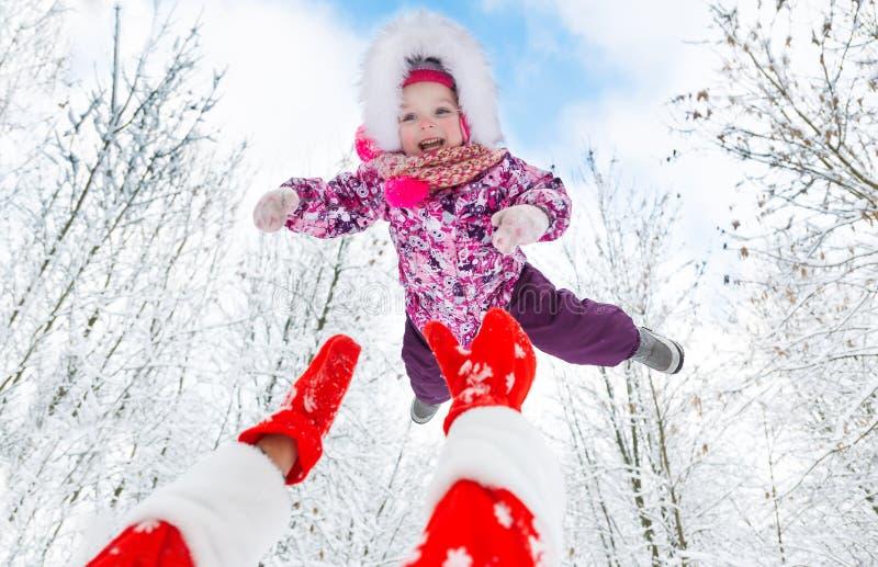 Santa Claus wirft oben obenliegendes nettes kleines Mädchen im Winterwald auf Weihnachten lizenzfreie stockfotografie