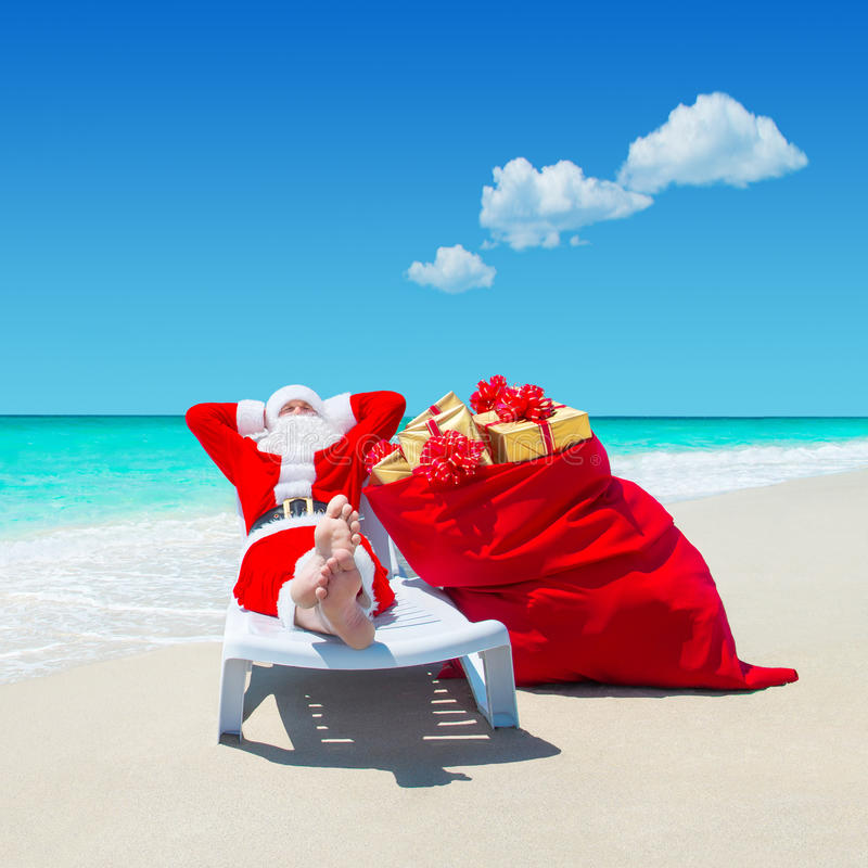 Free Santa Claus With Christmas Sack Full Of Gifts Relax On Sunlounger Barefooted At Perfect Sandy Ocean Beach. Stock Photo - 82913070