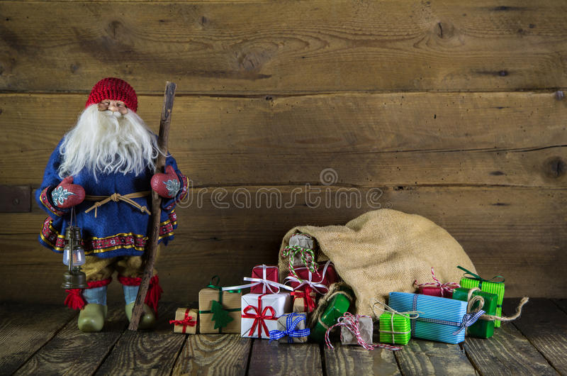 Santa claus on wooden background with colorful presents stock image