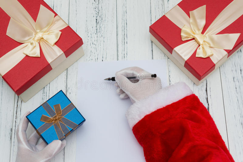 Santa Claus writing on a blank paper good for letter or advertisement and a gift box onher hand royalty free stock image