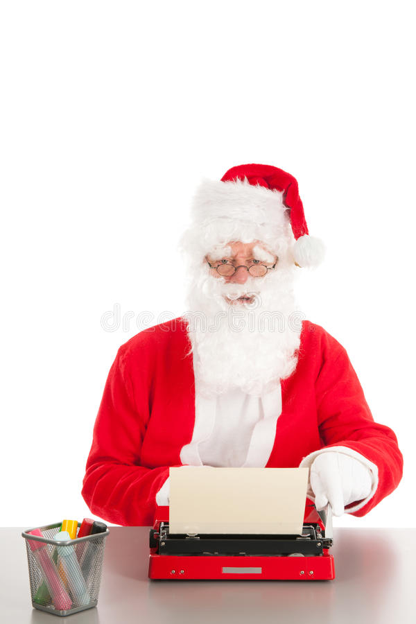 Santa Claus writing a letter. With old typewriter royalty free stock images