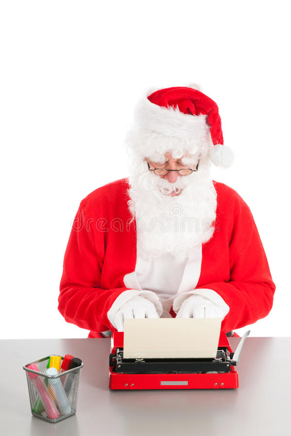 Santa Claus writing a letter. With old typewriter royalty free stock photo