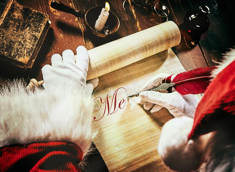 Santa Claus writing an Xmas greeting on a scroll. Santa Claus writing a Christmas greeting on an old scroll with a vintage quill feather pen in neat calligraphic stock photography