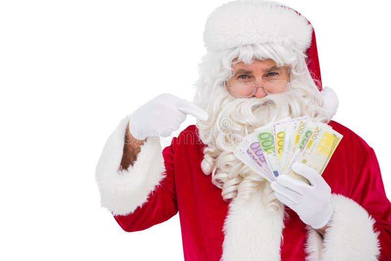 Santa Claus wskazuje jego gotówkowego zdjęcie stock