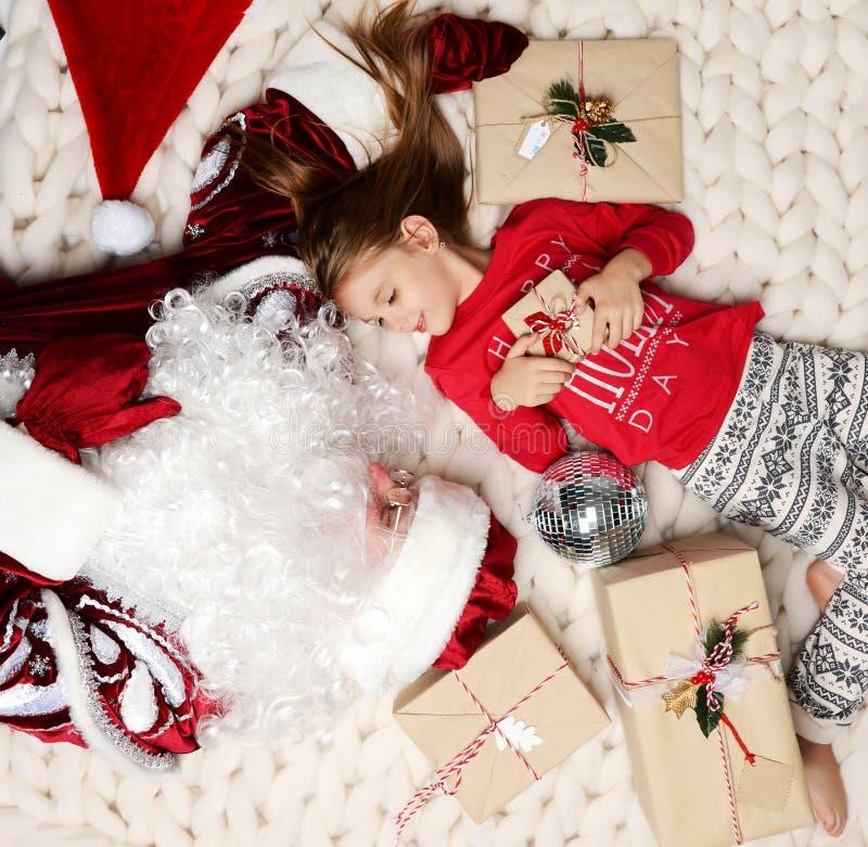Santa Claus y bebé que mienten en la manta de la Navidad con sonrisa rústica de los regalos del arte la actual foto de archivo libre de regalías