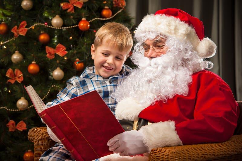 Santa Claus y un niño pequeño fotos de archivo