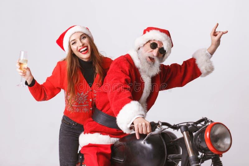Santa Claus And Young Mrs Claus Riding à motocicleta fotos de stock