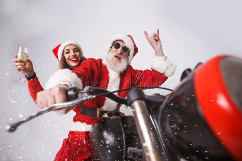 Santa Claus And Young Mrs Claus Riding à motocicleta imagem de stock