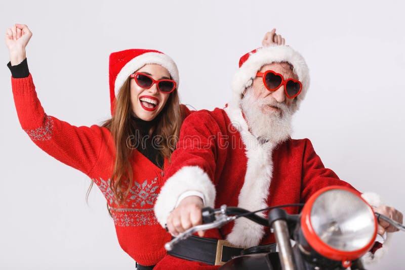Santa Claus And Young Mrs Claus Riding à motocicleta imagens de stock royalty free
