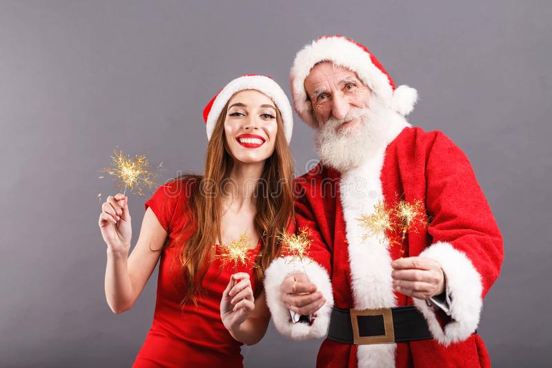 Santa Claus And Young Mrs Claus Standing With Sparklers On Gray Background arkivfoton