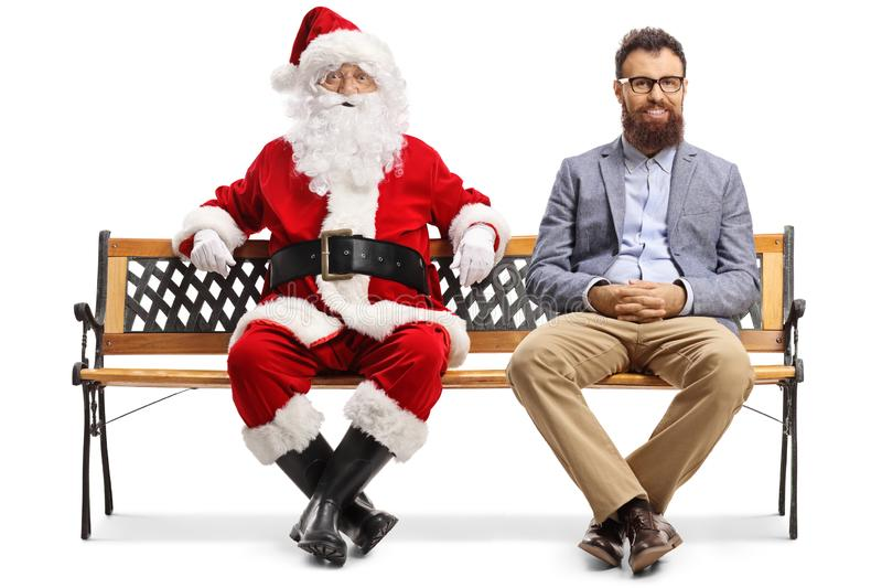 Santa Claus and a younger man sitting on a bench stock photography