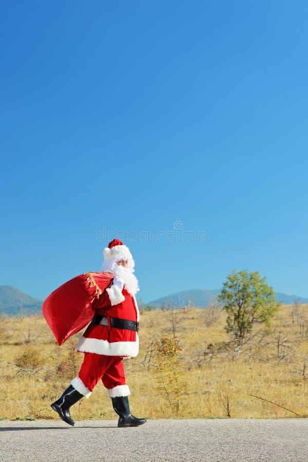 Santa Claus z torby odprowadzeniem na otwartej drodze zdjęcia stock