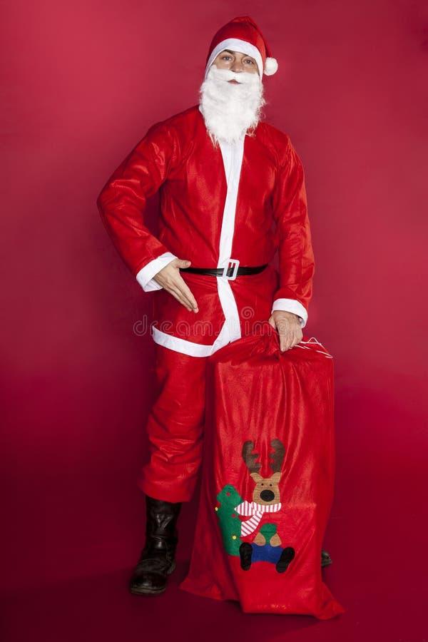 Santa Claus zeigt eine Tasche, die mit Geschenken angefüllt wird lizenzfreies stockbild