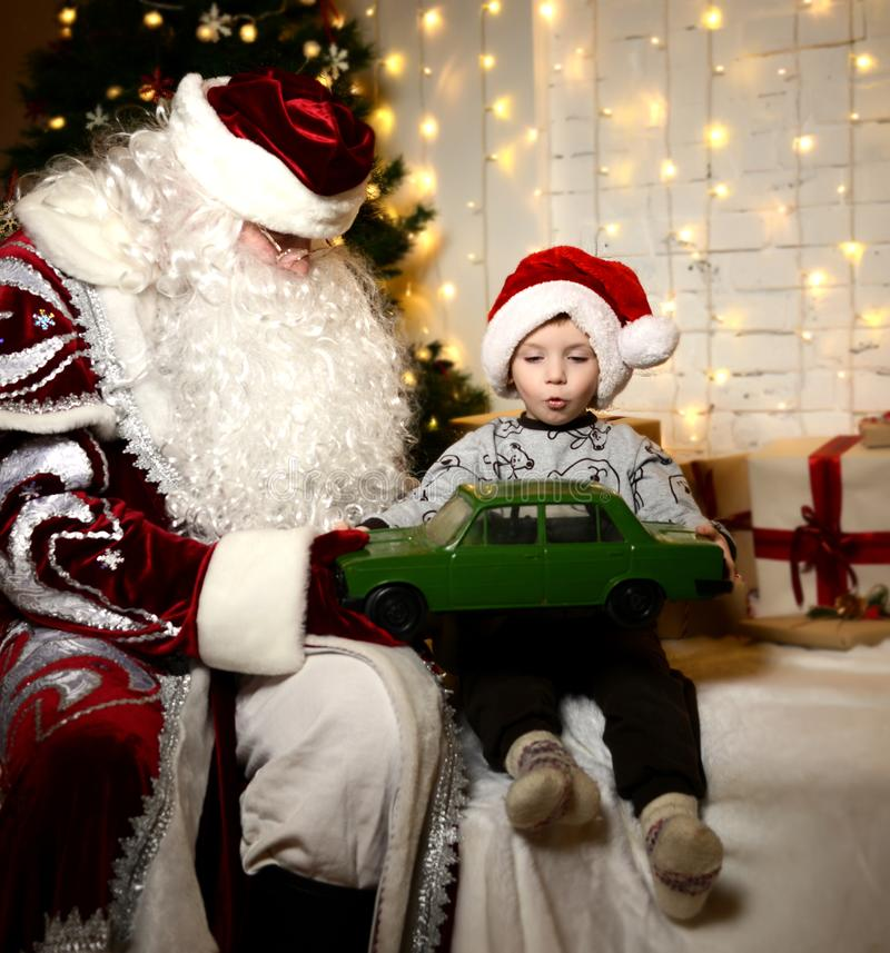 Santa Claus-zitting met gelukkig weinig leuk jong geitje van de babyjongen dichtbij Kerstboom stock afbeelding