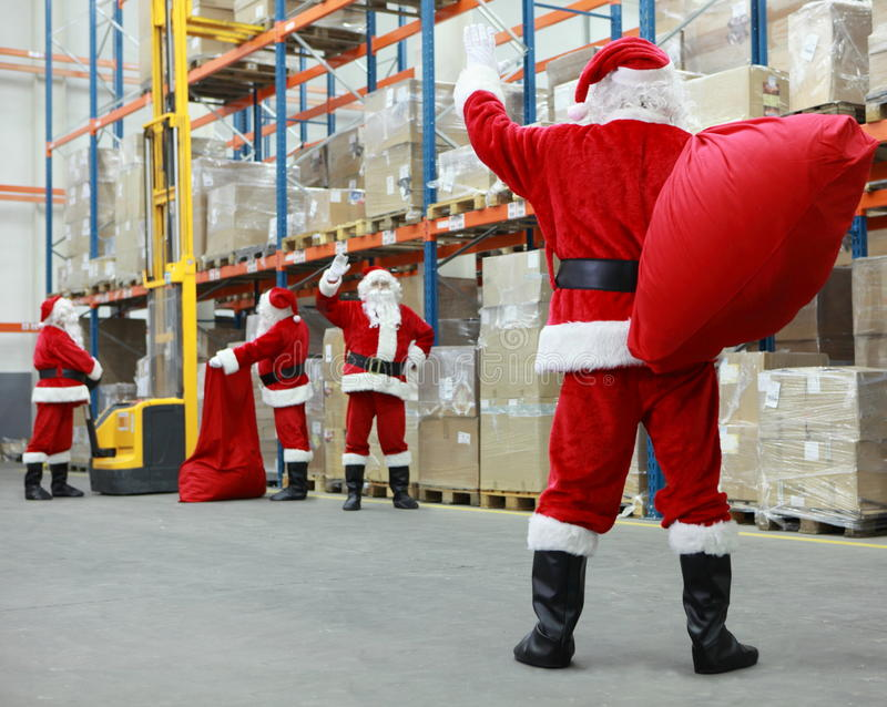 Santa Clausas team work. Group of santa clauses working together in storehouse royalty free stock photo