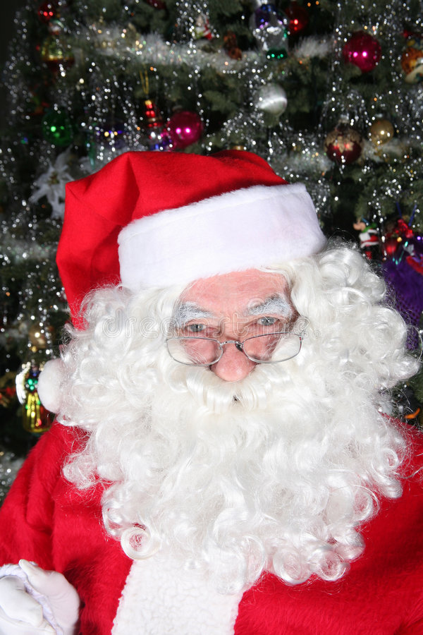 Santa clause. Sitting in front of a Christmas tree stock image