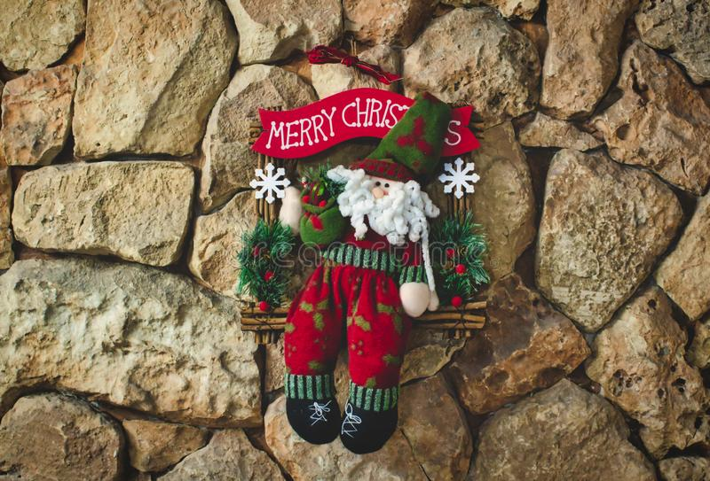 Santa clause Christmas decoration made with knitted wool hanging on a stone wall background royalty free stock images