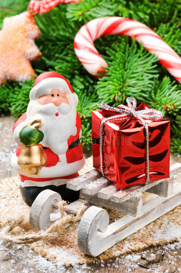 Santa Clause with Christmas gift. On wooden sledge royalty free stock photos