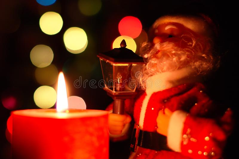 Santa Clause And Christmas Lights. Santa Clause with lamp, red burning candle and colorful bokeh in the background stock photo