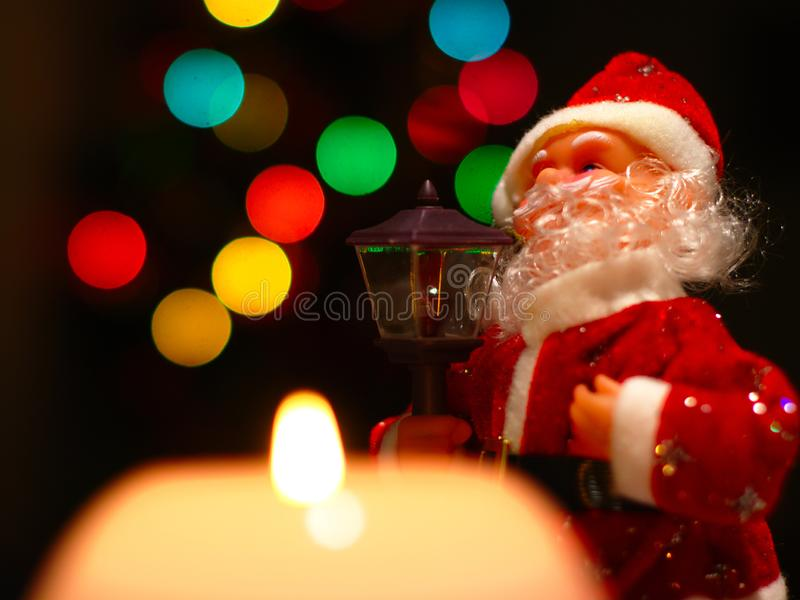 Santa Clause And Christmas Lights. Santa Clause with lamp, large pink burning candle and colorful bokeh in the background stock image