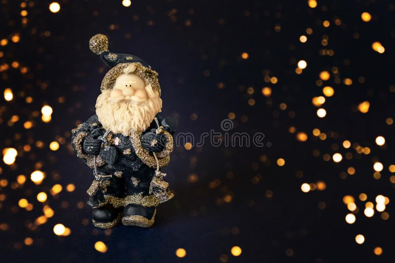 Santa Clause and Merry Christmas model figure toy on dark blue background with sparkles. Christmas, winter, new year concept. Copy stock photo