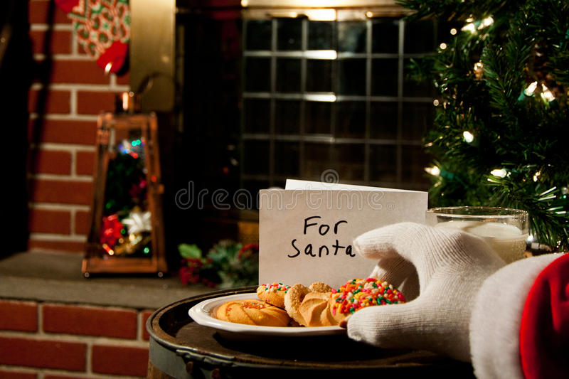 Santa Claus Taking A Cookie Royalty Free Stock Images